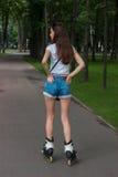 Тонкое брюнет предназначенное для подростков в джинсовой ткани замыкает накоротко катание в парке, rollerblading Стоковые Изображения RF
