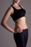 Тонкое тело женщины в спорт носит над серым цветом Стоковое фото RF
