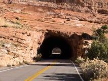 Тоннель через красный утес Стоковая Фотография