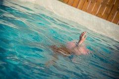 Тонуть рука маленькой девочки молодости поднятая underwater Стоковые Изображения RF