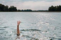 Тонуть человек Вставлять руку из воды стоковые фото