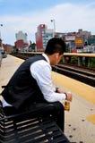 Топить, NY: Азиатская молодость слушая к iPod Стоковая Фотография RF