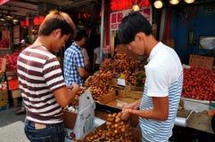 Топить, NY: Работники с плодоовощами Longan стоковая фотография rf