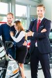 Торговец, клиенты и автомобиль в автосалоне Стоковое фото RF