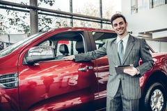 Торговец стоит около нового автомобиля в выставочном зале стоковая фотография