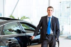 Торговец стоит около нового автомобиля в выставочном зале Стоковые Фото