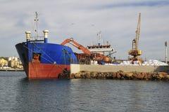 Торговое судно разгржая на док стоковое фото rf