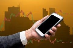Торгуя телефон владением бизнесмена умный и линия Grap валют торгуя стоковые фотографии rf
