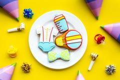 Торжество дня рождения ребенка с печеньями пряника на плите на желтом красочном взгляд сверху предпосылки Стоковое Фото