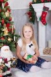 Торжество рождества или Нового Года Молодая красивая девушка в руках держа подарок рождества сидя около рождественской елки Firep Стоковое Изображение