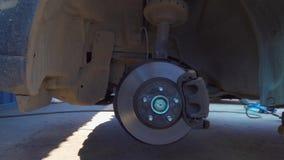 Тормозная шайба и автомобиль поднимают домкратом в обслуживании автомобиля автоматическом сток-видео