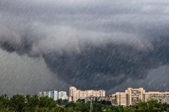 Торнадо, воронка заволакивает во время грозы ливень проливного дождя над городом стоковое фото rf