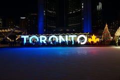 ТОРОНТО, КАНАДА - 2018-01-01: Люди перед ТОРОНТО подписывают с рождественской елкой в ноче осмотренной через кататься на коньках Стоковое Изображение