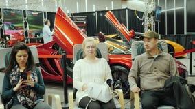 Торонто, Канада, 20-ое февраля 2018: Человек и женщина ослабляют в стульях массажа На большом автосалоне в Торонто сток-видео
