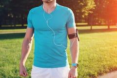 Торс спортсмена с умным вахтой и wristband в пустой cian футболке стоя в парке стоковое фото rf