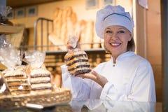 Торты губки зрелого работника хлебопекарни предлагая Стоковая Фотография RF