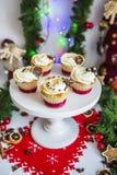 Торты, пирожные с высушенным лимоном и шоколад на белом постаменте на предпосылке зеленых гирлянды и светов рождества Стоковые Изображения RF