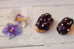 Торты eclair шоколада лежали на белом деревянном столе около 2 цветков орхидеи Стоковое Изображение