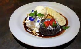 Торт лавы помадки шоколада украшенный с брызгать сахара замороженности, свежих клубник, банана и мороженого Стоковые Фотографии RF