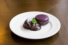 Торт лавы шоколада с macaroon и пиперментом на белой плите, Стоковое фото RF