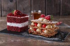 Торт бархата сладостного куска десерта feuille Mille красный с белый замораживать гарнирован с клубниками Стоковая Фотография RF