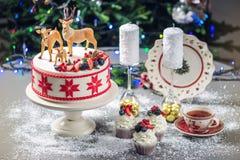 Торт белого рождества при красный орнамент на верхнем украшенный с диаграммами mastic оленей и свежих ягод на праздничной таблице Стоковая Фотография RF
