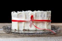 Торт белого шоколада связанный с белой и красной лентой в стеклянной пластинке лежит на деревянном столе На черной предпосылке Стоковое фото RF