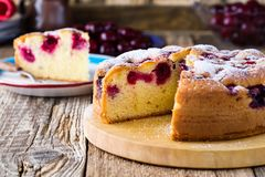 Торт вишни и кусок торта на деревенской таблице Стоковая Фотография