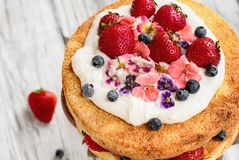 Торт губки Виктория с взбитой сливк с Candied цветками и свежими ягодами стоковые изображения rf
