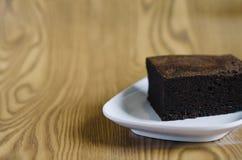 Торт губки шоколада в белой плите на деревянной предпосылке Стоковые Фотографии RF