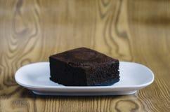 Торт губки шоколада в белой плите на деревянной предпосылке Стоковое Изображение RF