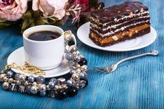 Торт губки шоколада с карамелькой и гайками на голубой предпосылке Стоковые Изображения RF