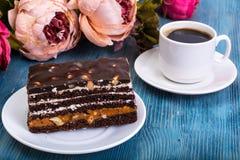 Торт губки шоколада с карамелькой и гайками на голубой предпосылке Стоковые Фотографии RF