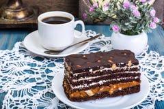 Торт губки шоколада с карамелькой и гайками на голубой предпосылке Стоковые Изображения