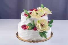 Торт домашней свадьбы 2-tiered украшенный с смородинами, клубниками и желтыми цветками Праздничный десерт ягоды Стоковое Изображение RF