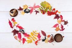 Торт, калина, черный chokeberry, красная рябина, листья осени и чашка кофе с молоком на светлой предпосылке Блюда глины Fl стоковая фотография