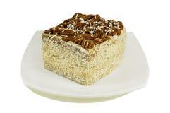 Торт кокоса на плите изолированной на белизне Стоковые Изображения