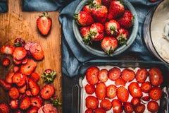 Торт клубники делая с отрезанными ягодами и сливк на темной деревенской предпосылке Стоковая Фотография