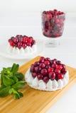 Торт меренги при сливк и клюквы украшенные с мятой на белой деревянной предпосылке Стоковое Изображение RF