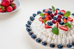 Торт меренги Pavlova при сливк и ягоды изолированные на белой предпосылке Стоковое Изображение