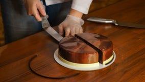 Торт мусса Праги Женщина режет кусок торта с кухонным ножом Яркие блески поливы зеркала вкусно Современный варить варить стоковое изображение