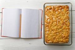 Торт песка с завалкой лимон-апельсина и меренга около тетради для рецептов Стоковые Фотографии RF