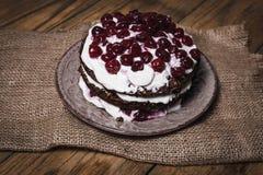 Торт пирожного с земной вишней на деревянной доске Стоковая Фотография