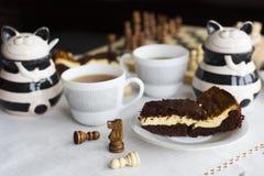 Торт пирожного шоколада на белой плите, 2 чашках чаю и шахматной доске Стоковые Фото
