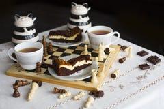 Торт пирожного шоколада на белой плите, 2 чашках чаю и шахматной доске Стоковая Фотография RF