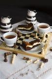 Торт пирожного шоколада на белой плите, 2 чашках чаю и шахматной доске Стоковые Фотографии RF