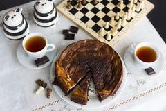Торт пирожного шоколада на белом торте плиты, пирожного шоколада на белой плите, 2 чашках чаю, 2 челюстях и шахматной доске Стоковая Фотография RF