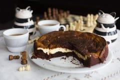 Торт пирожного шоколада на белом торте плиты, пирожного шоколада на белой плите, 2 чашках чаю, 2 челюстях и шахматной доске Стоковое фото RF