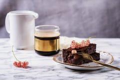 Торт пирожного шоколада с ягодами красной смородиной и чашкой кофе Стоковые Фото