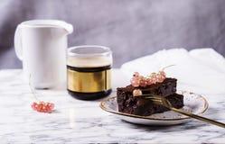 Торт пирожного шоколада с ягодами красной смородиной и чашкой кофе Стоковые Изображения RF